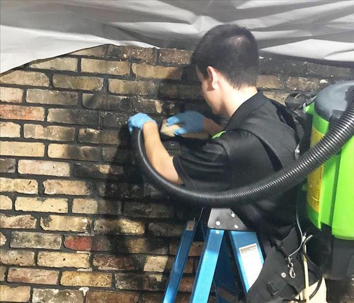 worker cleaning soot from brick wall.